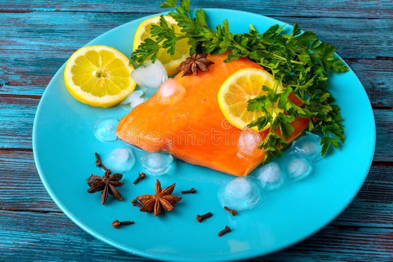 Stück rote Fischlügen auf einer Platte mit einer Zitrone stockfotos
