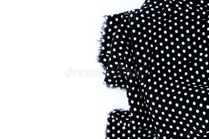 Stück schwarzes Gewebe mit einem Muster von weißen Erbsen, an lokalisiert stockfotografie
