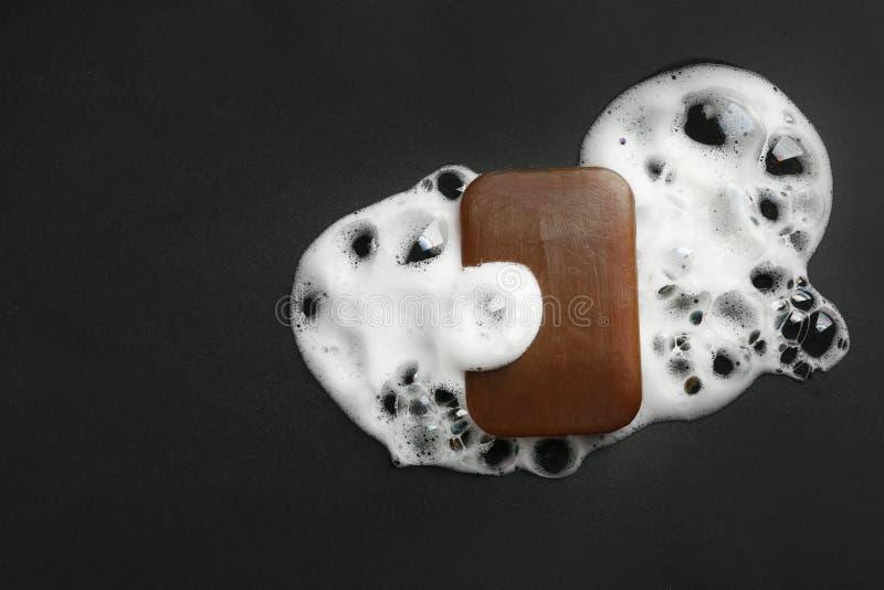 Stück Seife und Schaum auf schwarzem Hintergrund, Draufsicht lizenzfreie stockfotos