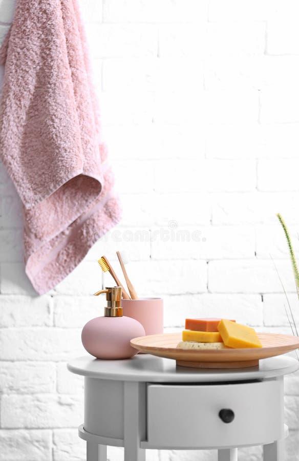 Stück Seifen, Shampoo und Toilettenartikel auf Tabelle im Badezimmer lizenzfreie stockfotografie