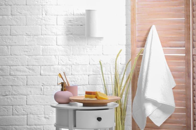 Stück Seifen, Shampoo und Toilettenartikel auf Tabelle im Badezimmer stockfotografie
