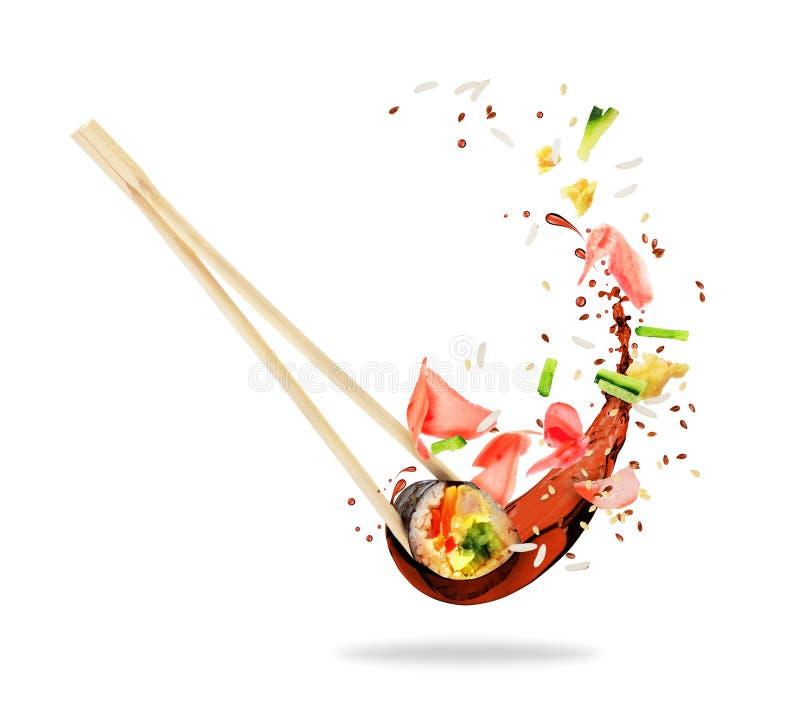 Stück Sushi eingeschoben zwischen Essstäbchen mit Sojasoße lizenzfreie stockfotos