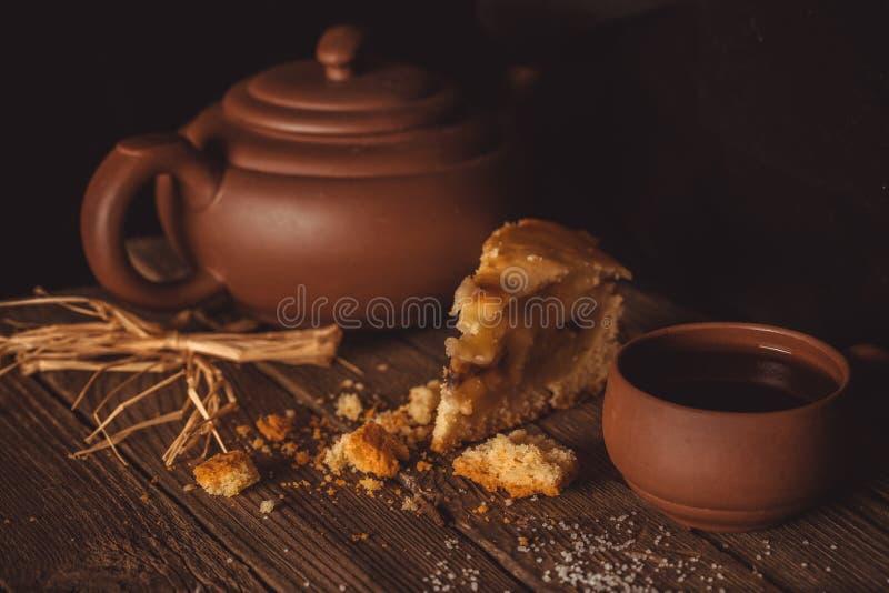 Stück Torte und Tonwaren für Tee auf einem alten Holztisch stockfoto