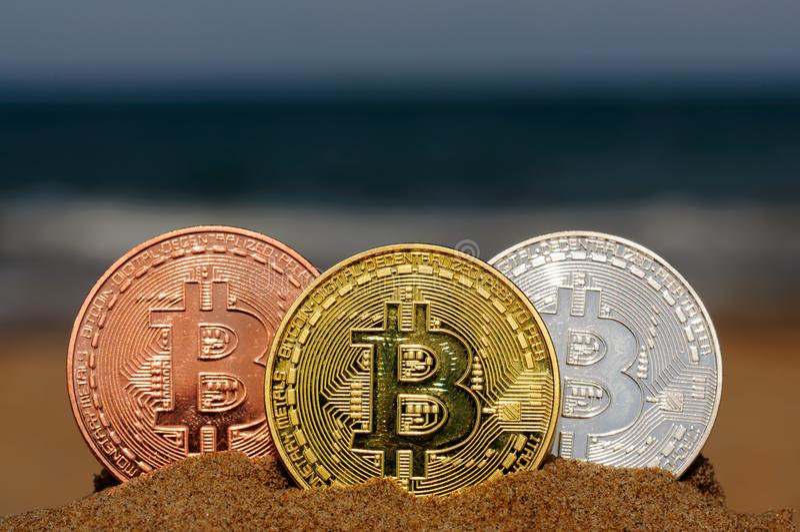 Stückchenmünzengold, -silber und -bronze prägen und druckten verschlüsseltes Geld, Kryptawährungskonzept in einem Strandsand lizenzfreie stockfotografie