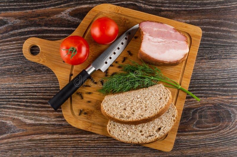 Stücke Brot, geräuchertes Bruststück, Tomaten, Dill und Gewürze, Messer auf Schneidebrett auf Holztisch Beschneidungspfad eingesc stockbilder