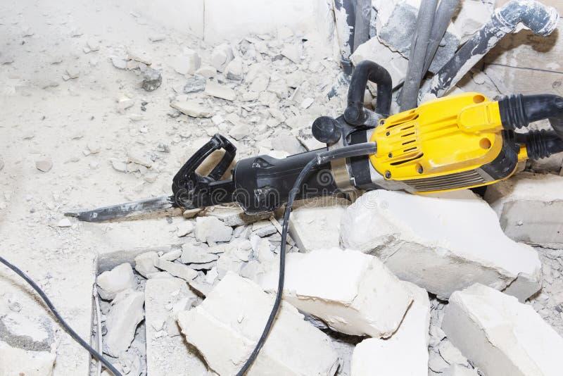 Stücke der defekten Wand nahe bei dem Jackhammer lizenzfreies stockbild