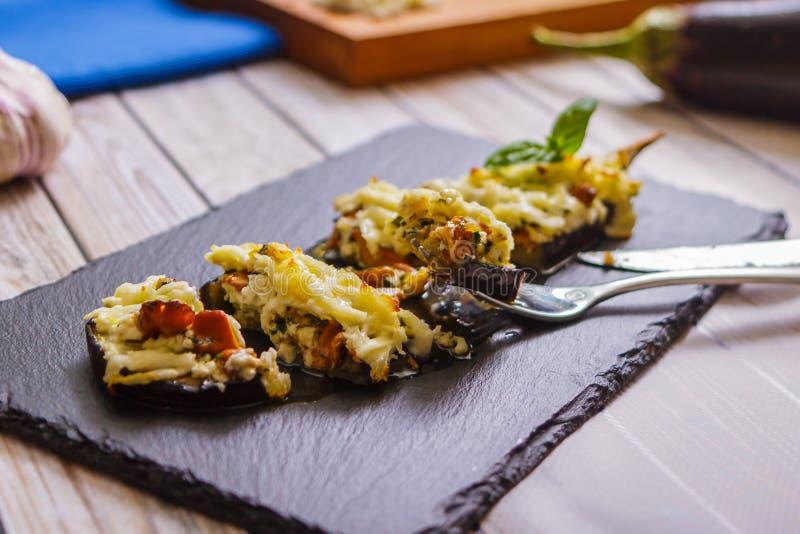 Stücke der gebackenen Aubergine mit Pilzen und Käse auf Schiefer stockfotos