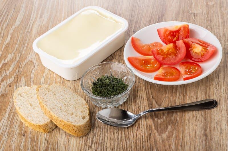 Stücke der Tomate, Brot, Schüssel mit Dill, Plastikglas mit geschmolzenem Käse, Löffel auf Holztisch lizenzfreie stockfotografie
