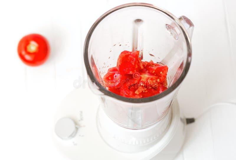 Stücke der Tomate in einer Mischmaschine Tomate, Tomate, Pfeffer, Knoblauchlüge auf einem hölzernen Hintergrund lizenzfreies stockbild