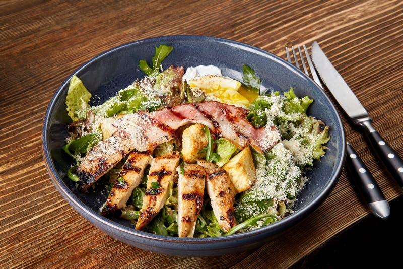 Stücke des Huhns mit Reis, Pfirsich und Petersilie in der weißen Schüssel getrennt auf weißem Hintergrund Huhn Caesar Salad Caesa lizenzfreies stockfoto