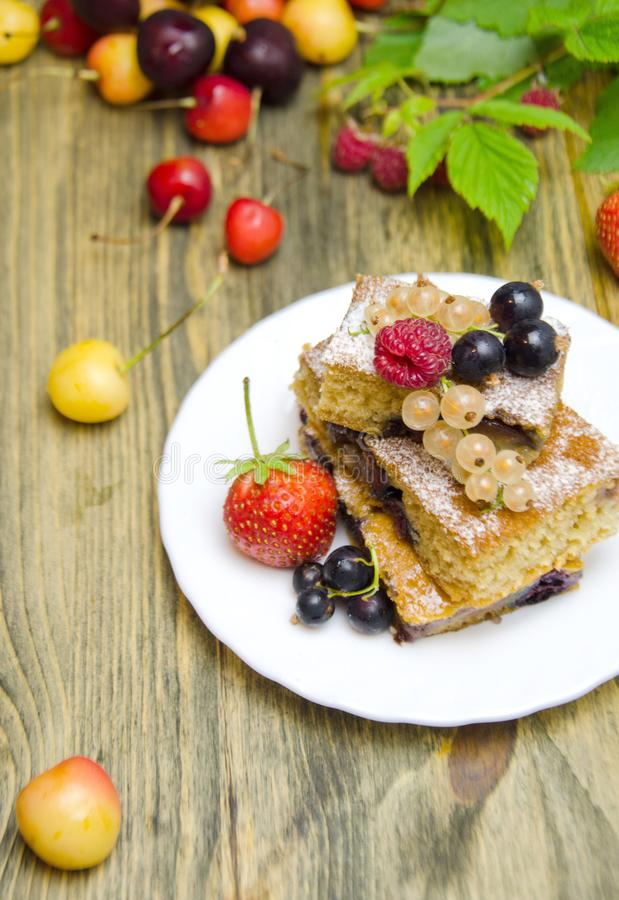 Stücke des Kuchens mit Beeren und frischen Erdbeerkorinthen- und -kirschbeeren auf hölzernem Hintergrund lizenzfreie stockfotos