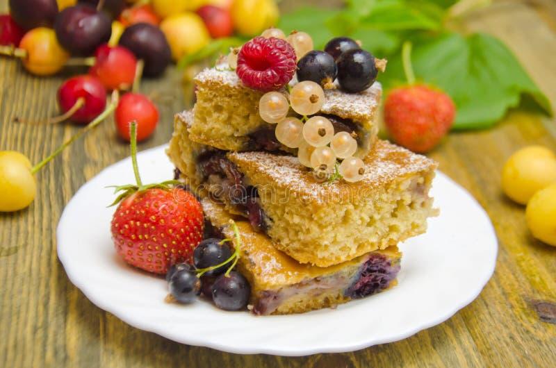 Stücke des Kuchens mit Beeren und frischen Erdbeerkorinthen- und -kirschbeeren auf hölzernem Hintergrund stockfoto