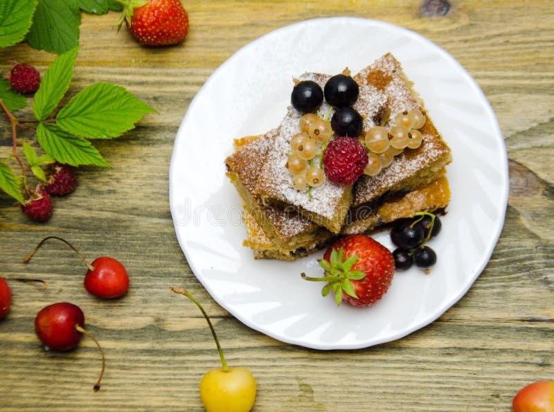 Stücke des Kuchens mit Beeren und frischen Erdbeerkorinthen- und -kirschbeeren auf hölzernem Hintergrund lizenzfreie stockbilder