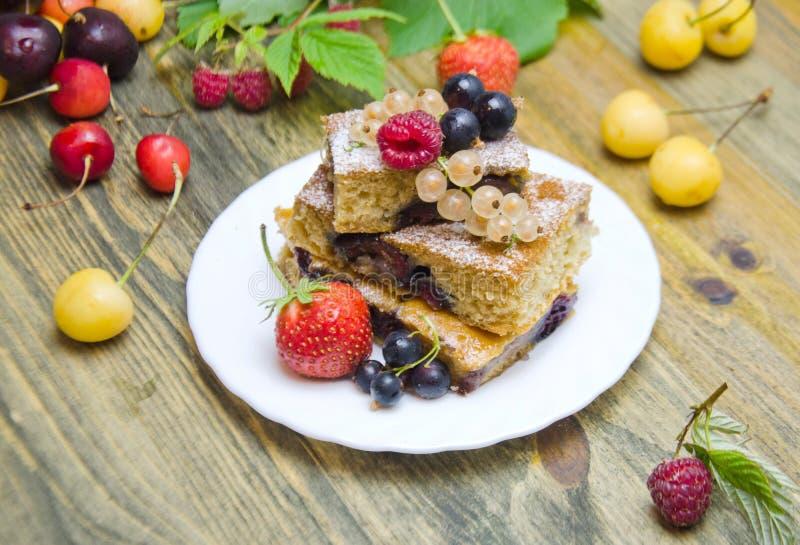 Stücke des Kuchens mit Beeren und frischen Erdbeerkorinthen- und -kirschbeeren auf hölzernem Hintergrund stockbild