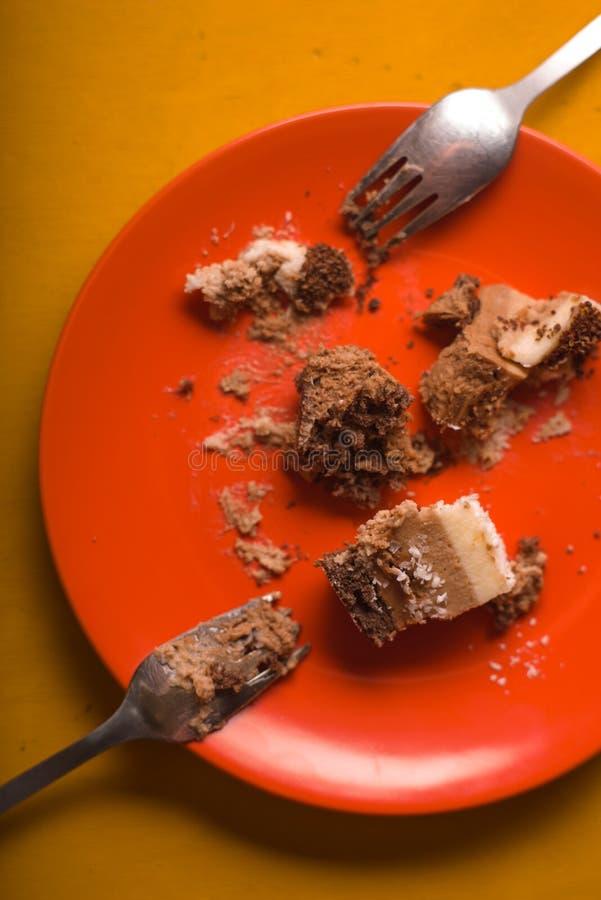 Stücke des Schokoladenkuchens mit Kokosnuss bricht auf einer orange Platte ab stockbilder