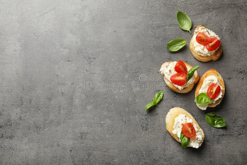 Stücke des Stangenbrots mit geschmackvollem Frischkäse und Tomaten auf grauer Tabelle, flache Lage lizenzfreie stockbilder