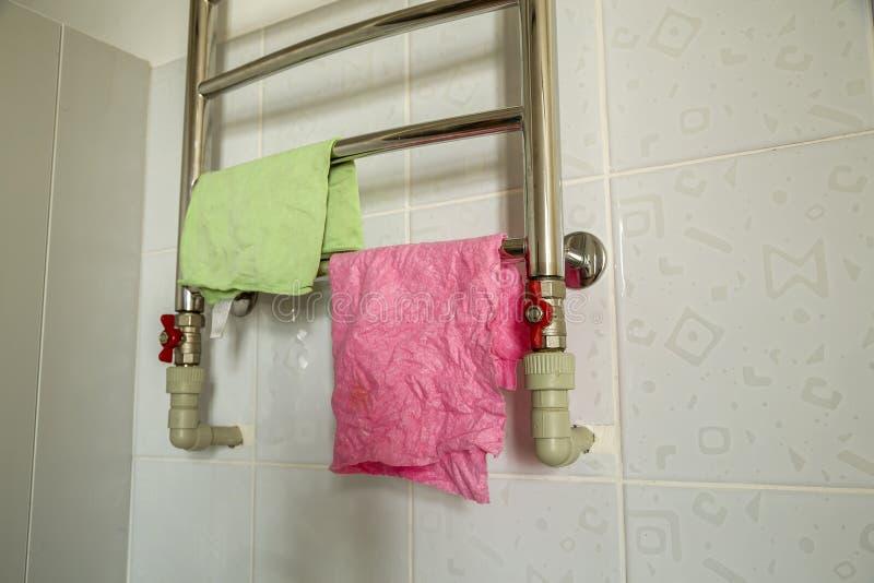 Stücke des Stoffes trocknend auf Badezimmerheizungs-Handtuchhalterheizkörper Handtuchhalteredelstahlregal stockfoto