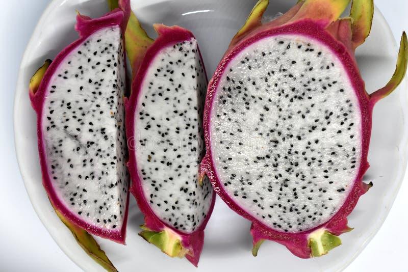 Stücke Drachefrucht auf weißer Platte stockfotografie