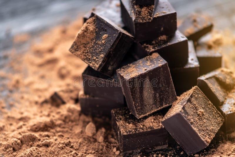 Stücke dunkle Bitterschokolade mit Kakaopulver auf dunklem hölzernem Hintergrund Konzept von Süßigkeitenbestandteilen lizenzfreie stockfotos