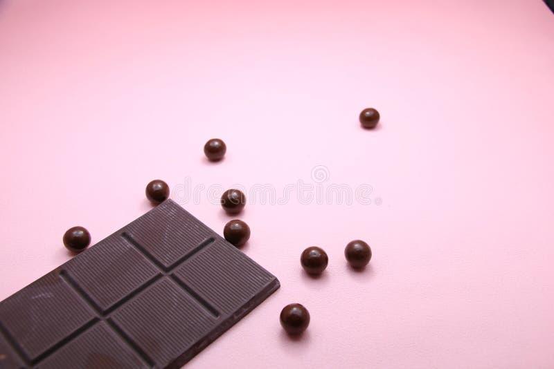Stücke dunkle Schokoriegel- und Milchschokoladeperlen auf rosa Hintergrund, Draufsicht, Kopienraum lizenzfreies stockbild