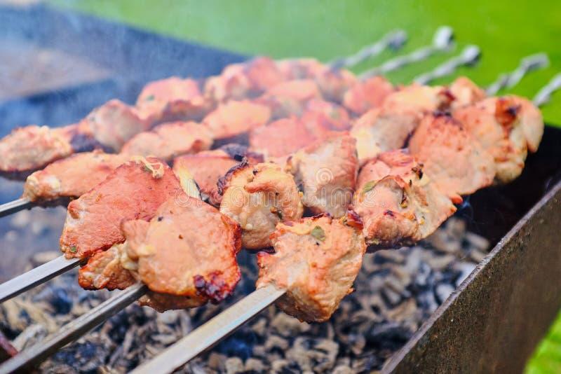 Stücke Fleisch werden auf Feuer auf Aufsteckspindeln gebraten stockbilder