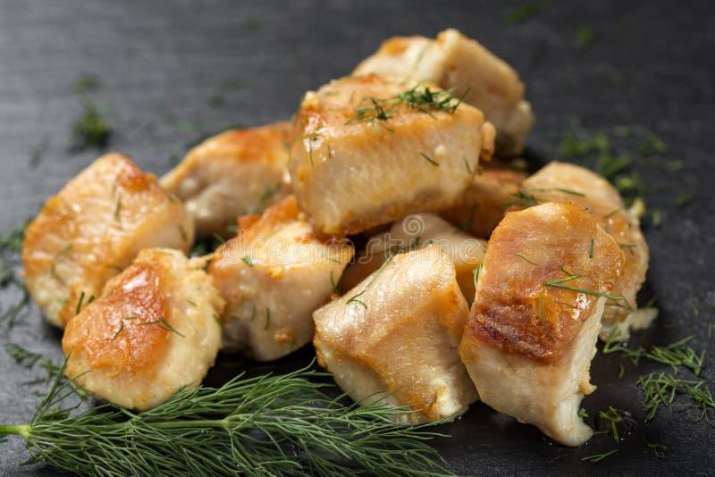 Stücke gebratenes Hühnerbrustfleisch auf einem dunklen Schiefer mit grünem d lizenzfreies stockbild