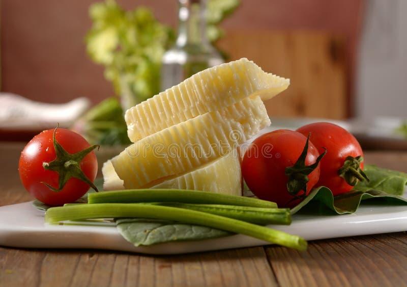 Stücke italienischer salziger Käse mit Kirschtomate im Schneidebrett lizenzfreie stockfotos