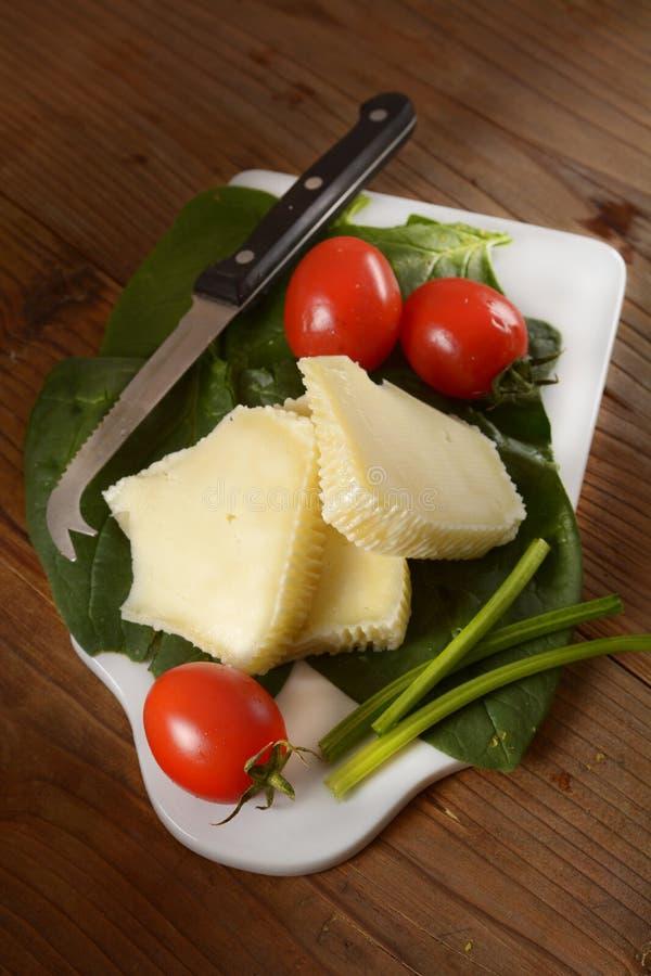 Stücke italienischer salziger Käse mit Kirschtomate im Schneidebrett stockfoto
