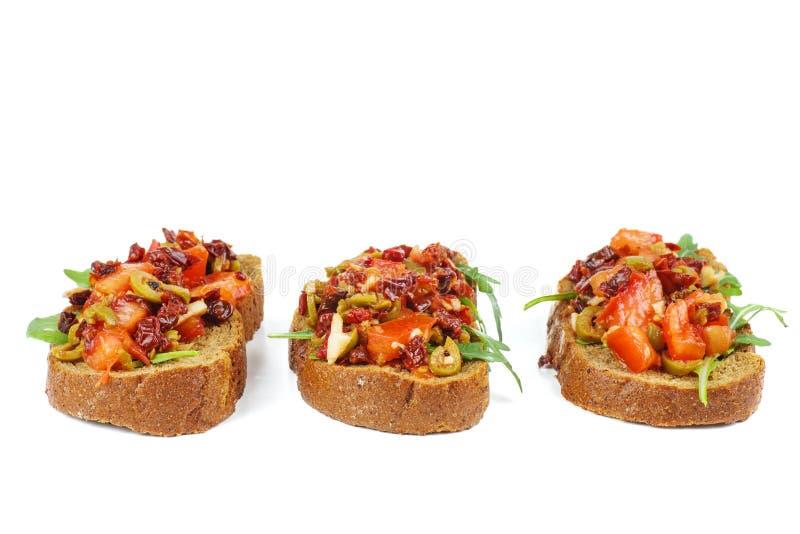 Stücke Roggenbrot mit dem Käse, getrockneten Tomaten, Oliven und Gemüse lokalisiert auf weißem Hintergrund lizenzfreies stockfoto