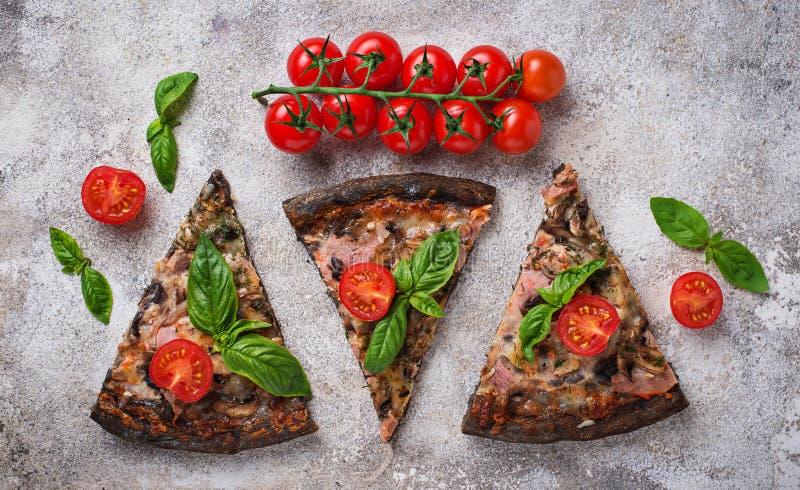 Stücke schwarze Pizza mit Tomaten und Basilikum stockfotografie