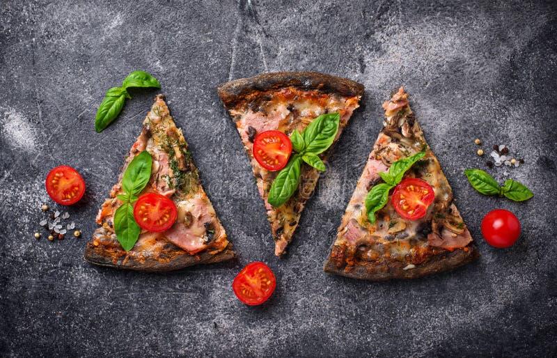 Stücke schwarze Pizza mit Tomaten und Basilikum lizenzfreies stockbild