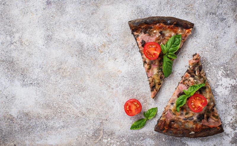 Stücke schwarze Pizza mit Tomaten und Basilikum stockfotos