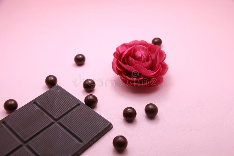 Stücke von von dunklen von Schokoriegel- und Milchschokoladeperlen und -Valentinsgrüßen stiegen auf rosa Hintergrund, Draufsicht, lizenzfreie stockfotografie
