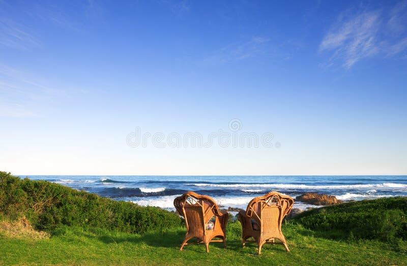 Stühle in dem Meer stockfotos