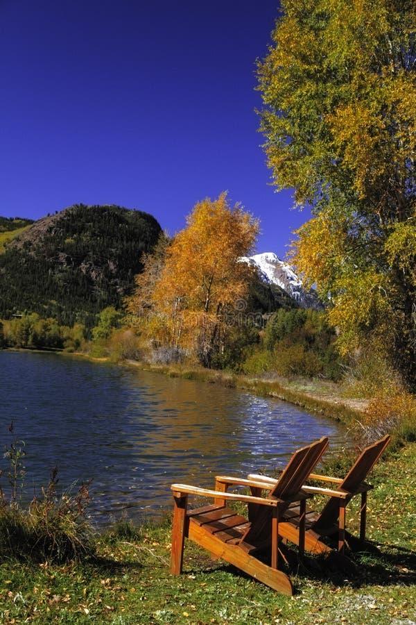 Stühle durch See lizenzfreie stockfotografie