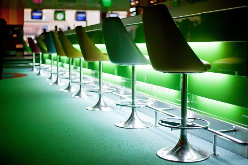 Stühle im Stab mit grünen Leuchten lizenzfreie stockfotos