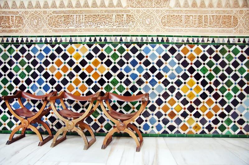 Stühle und die Wand von Fliesen im Alhambra lizenzfreie stockfotografie