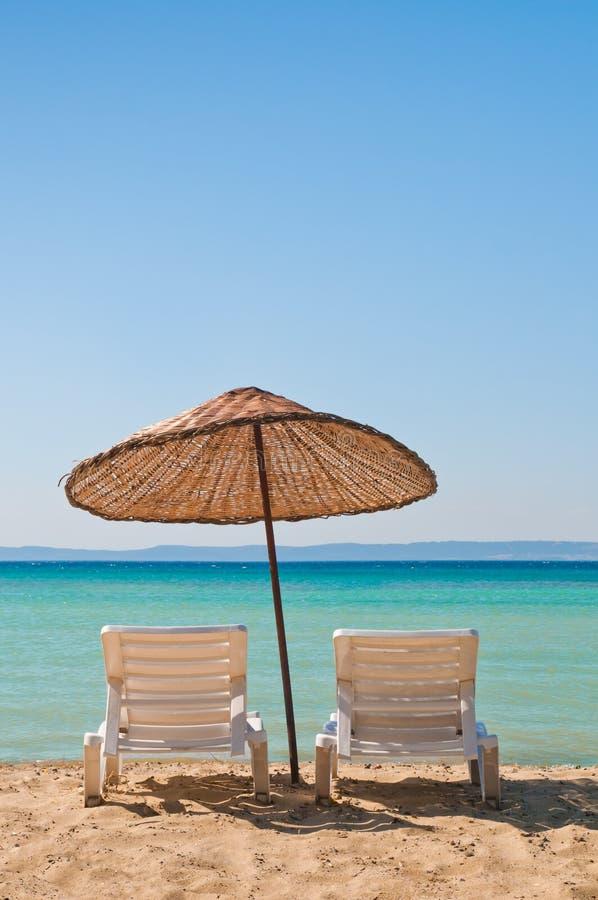 Stühle und Regenschirm auf einem Strand stockfotografie