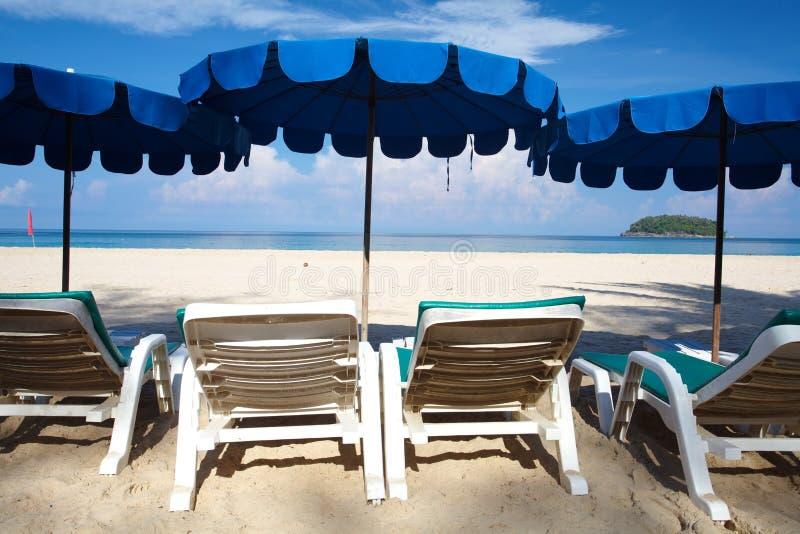 Stühle und Regenschirm auf Strand lizenzfreies stockfoto