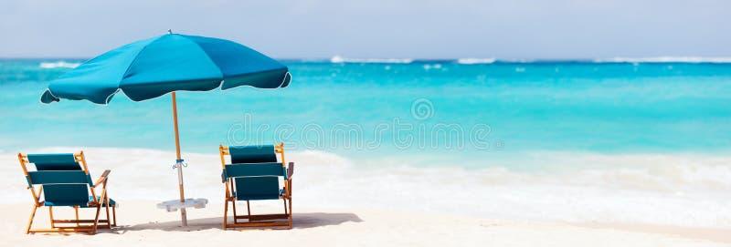 Stühle und Regenschirm auf tropischem Strand lizenzfreie stockbilder