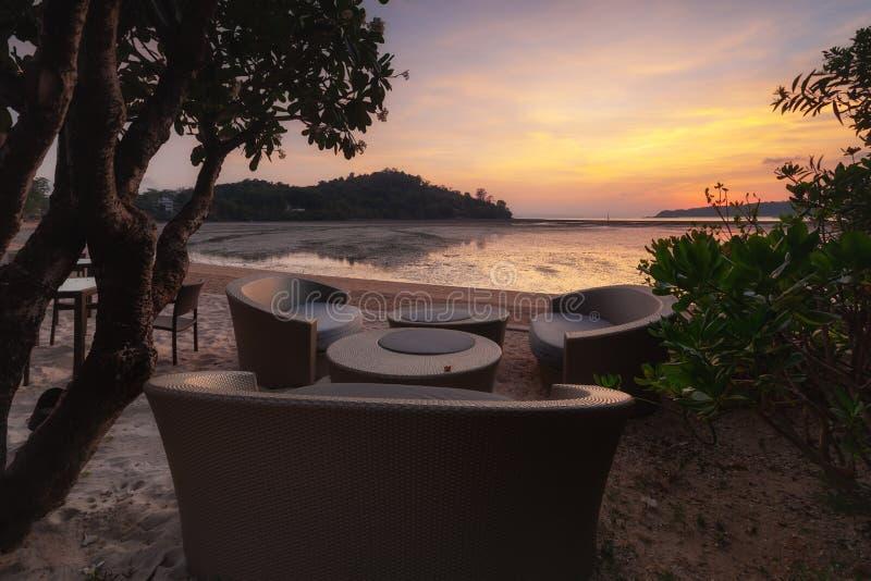 Stühle und Regenschirm im tropischen sandigen Strand stockfotografie