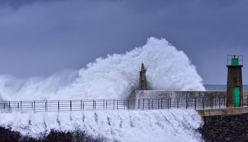 Stürmische Welle über altem Leuchtturm und Pier von Viavelez stockfotografie