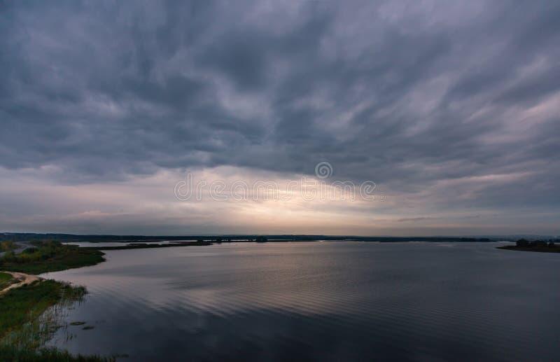 Stürmischer bewölkter Himmel bei Sonnenuntergang über dem Fluss Volga lizenzfreie stockfotos