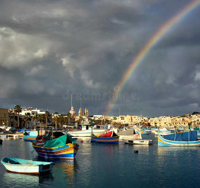 Stürmischer Tag in Marsaxlokk-Hafen, in den schweren Wolken und im Regenbogen lizenzfreie stockfotos
