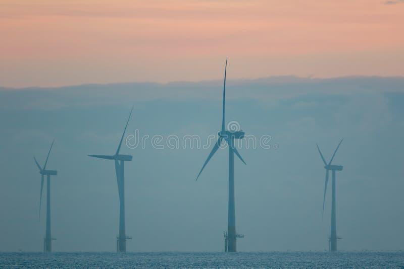 Stützbare Betriebsmittel Nebelhafte Morgenwindparkturbinen pastell lizenzfreie stockfotos