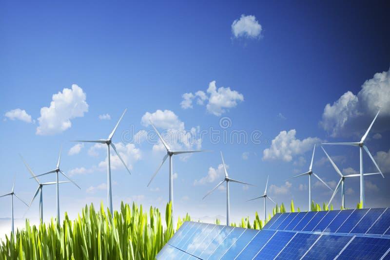 Stützbares Konzept der natürlichen Energie mit Flügelturbinen und photo-voltaischer Platte unter blauem Himmel stockbilder