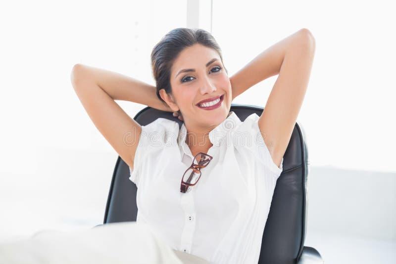 Stützende Geschäftsfrau, Die An Ihrem Schreibtisch Lächelt An Der Kamera Sitzt Lizenzfreie Stockbilder