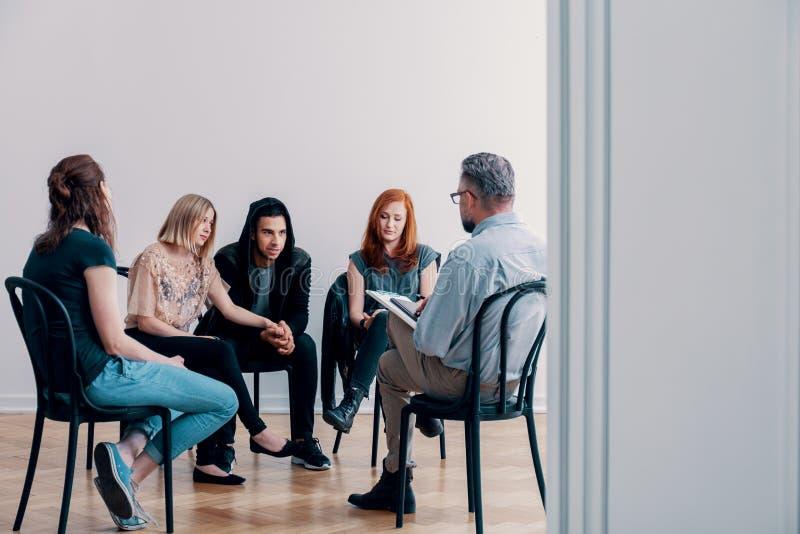 Stützungskonsortium, das in einem Kreis sitzt und mit einem Psychiater spricht lizenzfreie stockfotografie
