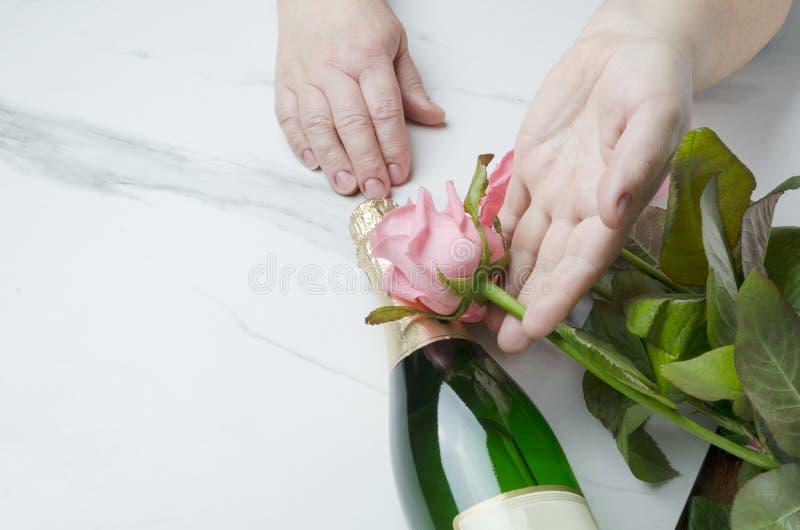St华伦泰` s天概念 得到的妇女当前为玫瑰情人节花束  浪漫晚餐的香宾 免版税库存图片