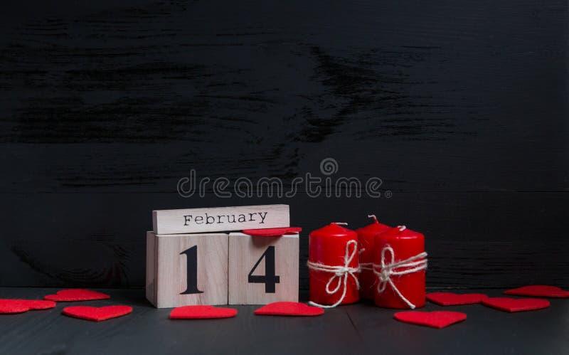 St华伦泰` s天概念 日历与数字和月在与红色蜡烛的黑木背景放置 库存照片